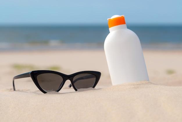 Crema solare e occhiali da sole nella sabbia in una giornata di sole in spiaggia.