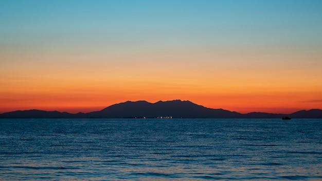 Tramonto sul mare egeo, nave e terra in lontananza, acqua, grecia