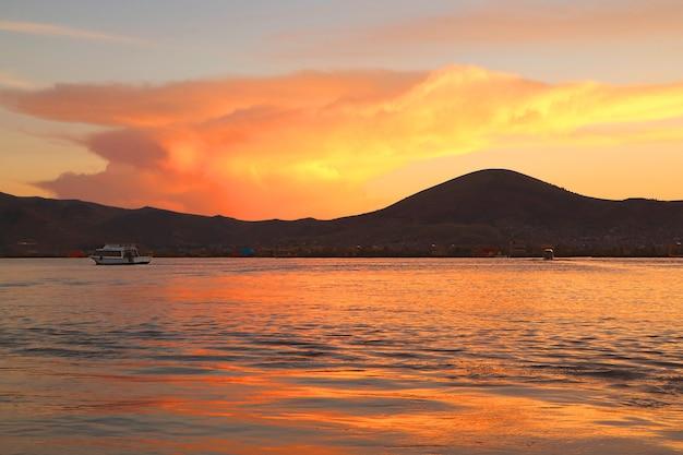 Afterglow del tramonto che riflette sul lago titicaca, il lago navigabile più alto del mondo a puno, in perù