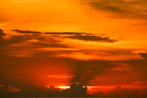 Tramonto indietro sull'ultima nuvola arancione-rosso-chiaro della siluetta del cielo