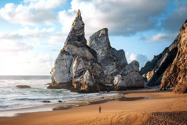 Tramonto sulla spiaggia di ursa a sintra con un uomo che passeggia tra le rocce sulla costa del portogallo