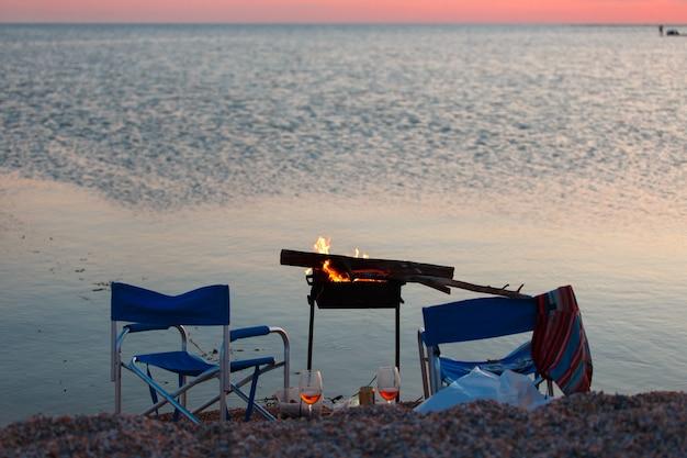 Tramonto sulla spiaggia con barbecue, due sedie da campeggio e un paio di bicchieri di birra o vino.
