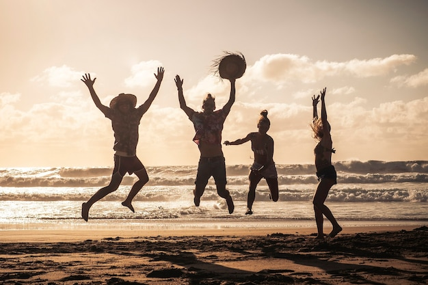 Tramonto in spiaggia con un gruppo felice di giovani che saltano divertendosi - amici in vacanza estiva che si divertono insieme in amicizia - stile di vita sabbioso e concetto di viaggio turistico