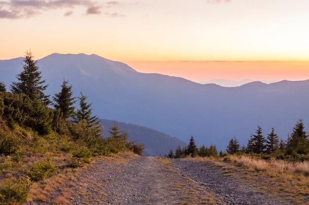 Tramonto in montagne carpatiche con una strada sterrata di fronte