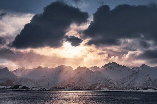 Tramonto in nuvoloso sulla catena montuosa innevata nell'isola di senja, norvegia