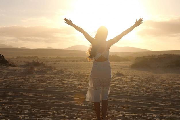 Tramonto nel deserto. giovane donna con le braccia alzate che indossa un abito bianco che cammina nella sabbia delle dune del deserto durante il tramonto. ragazza sulla sabbia dorata su corralejo dunas, fuerteventura.