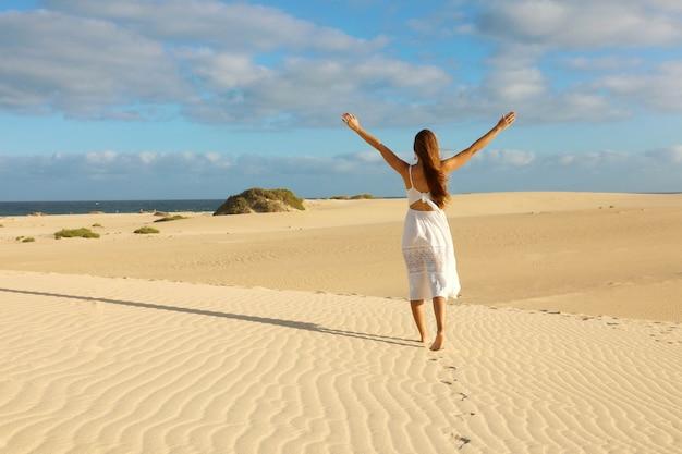 Tramonto nel deserto. giovane donna con con le braccia alzate che indossa un abito bianco che cammina nella sabbia delle dune del deserto durante il tramonto. ragazza sulla sabbia dorata su corralejo dunas, fuerteventura.
