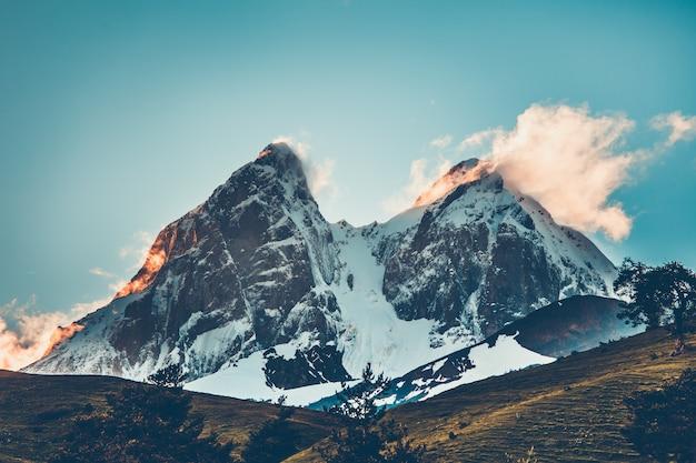 Vista di sera di tramonto sopra il picco di montagna nevoso