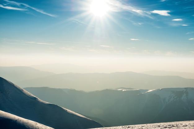 Tramonto su colline e montagne con la neve
