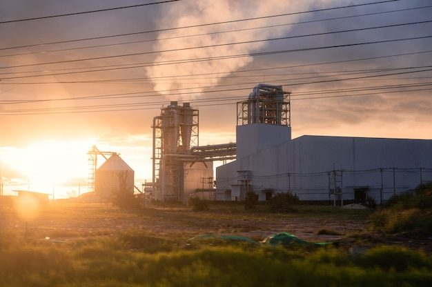Tramonto sulla costruzione di tubi industriali della fabbrica di fibra di legno che lavora con il rilascio di fumo dal camino in campagna