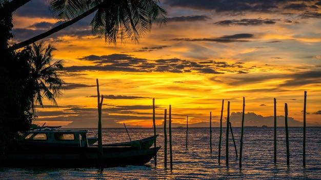 Tramonto sull'isola di kri. alcune barche in primo piano. raja ampat, indonesia, papua occidentale.