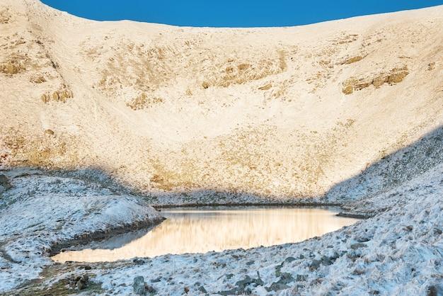 Tramonto al lago in montagna d'inverno. acqua blu con riflesso del cielo.
