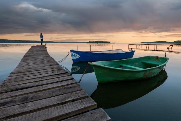 Tramonto sul lago con barche e una ragazza in piedi sul molo e vagando in lontananza