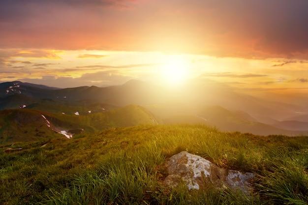 Paesaggio al tramonto con prato di erba verde, alte vette e valle nebbiosa sotto il vivace cielo serale colorato nelle montagne rocciose.
