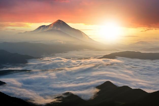 Paesaggio al tramonto con alte vette e vallata nebbiosa con spesse nuvole bianche sotto il cielo di sera colorato vibrante in montagne rocciose.