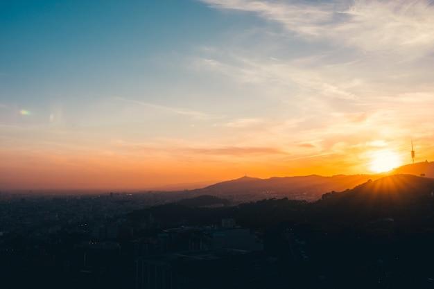 Un tramonto in montagna con la città di barcellona