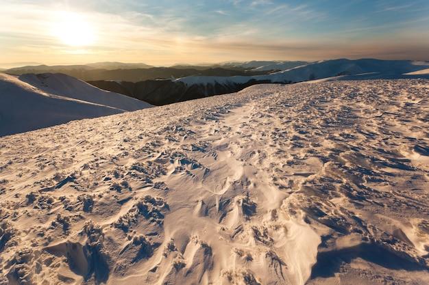 Tramonto su montagne coperte di neve in inverno chiaro giorno o tramonto