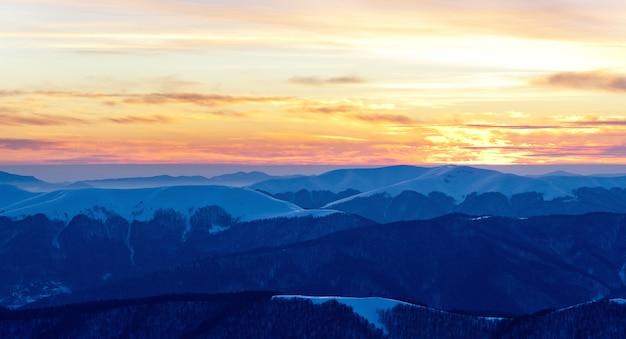 Tramonto sulle cime delle montagne coperte di neve in una giornata invernale limpida o al tramonto