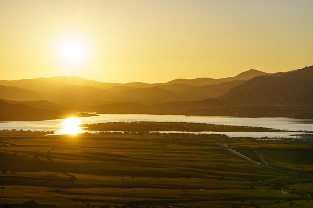 Tramonto in montagna con lago d'acqua nella valle e raggi di sole nel cielo blu. navacerrada madrid. spagna.