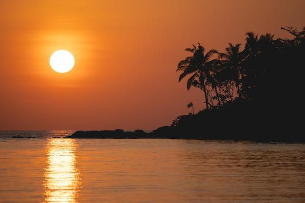 Vista sull'oceano al tramonto. sole sopra il mare sul cielo arancione.