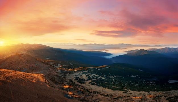 Panorama al tramonto in una valle di montagna con nuvole basse. drammatico paesaggio con cielo al tramonto, montagne e nebbia.