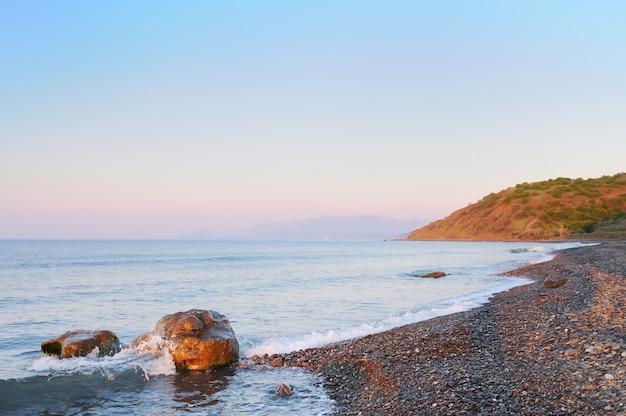 Tramonto in riva al mare, spiaggia rocciosa