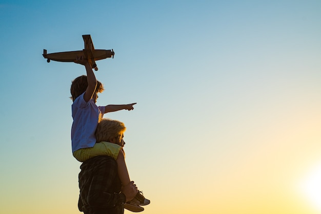 Siluetta al tramonto di padre felice e figlio del bambino con l'aeroplano sogna di viaggiare. bambino felice del ragazzo.