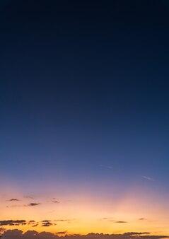 Cielo di tramonto verticale la sera al crepuscolo con raggi di sole colorati