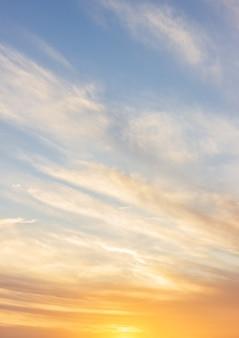 Cielo al tramonto verticale la sera con nuvole colorate di luce solare