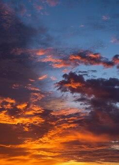 Cielo di tramonto verticale con luce solare colorata sul cielo blu scuro.