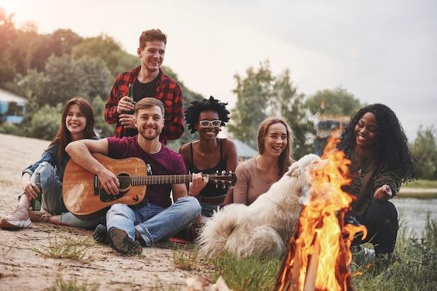 All'ora del tramonto. un gruppo di persone fa un picnic sulla spiaggia. gli amici si divertono nel fine settimana.