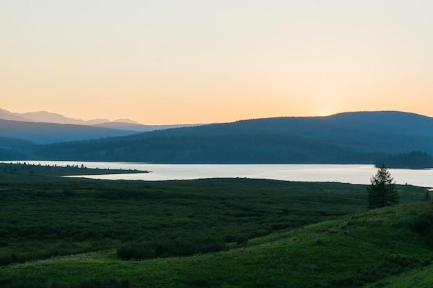 Tramonto nella valle di un lago di montagna. un bellissimo lago di montagna con canneti circondato da catene montuose e foreste impenetrabili.