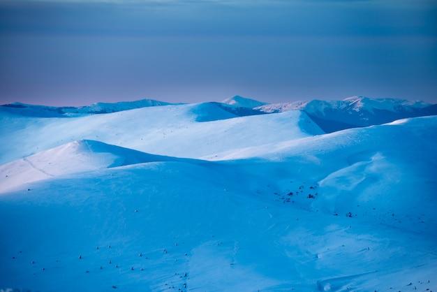 Tramonto in montagne invernali ricoperte di neve