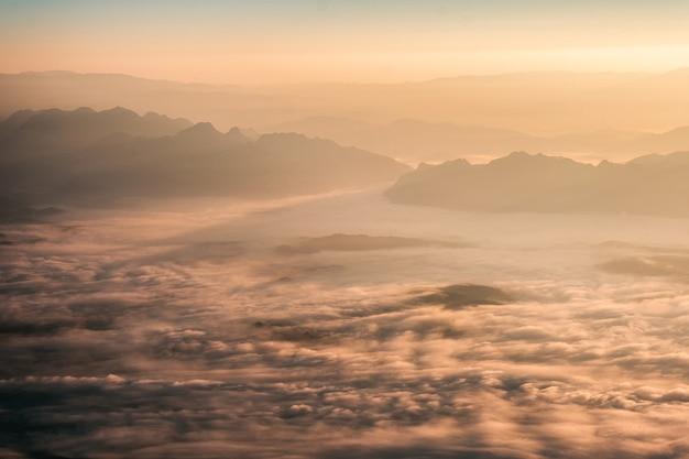 Sole sulla catena montuosa con nebbia nel parco nazionale al mattino