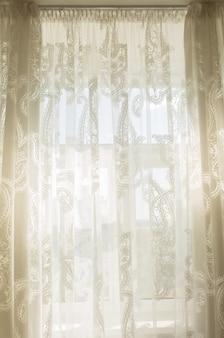 Sole attraverso le tende di tulle trasparente in camera con finestra