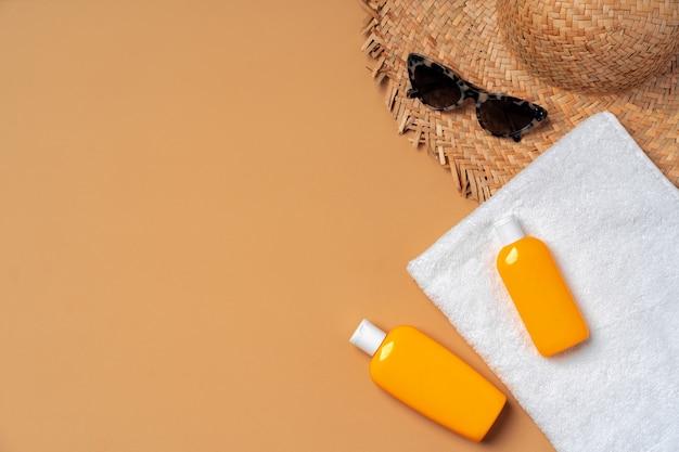 Prodotto cosmetico abbronzante con asciugamano, cappello e occhiali da sole su beige, piatto
