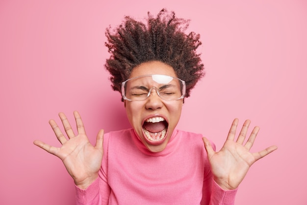 La donna afroamericana emotiva super eccitata impazzisce e urla con la bocca spalancata tiene i palmi alzati ha i capelli ricci in piedi indossa occhiali trasparenti e maglione rosa. concetto di emozioni