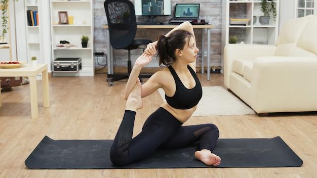 Super flessibile giovane donna seduta sul tappetino da yoga in soggiorno.