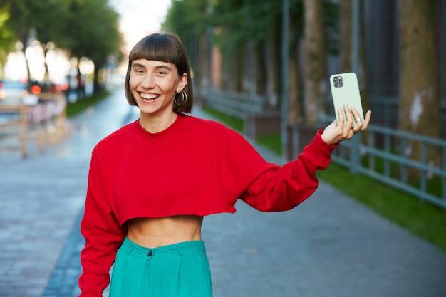 Super felice donna millenaria che tiene il telefono in strada, donna carina hipster in maglione rosso alla moda con smartphone