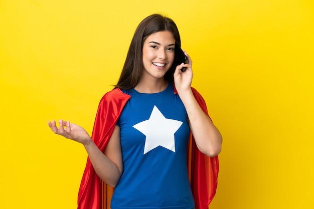 Super eroe donna brasiliana isolata su sfondo giallo che tiene una conversazione con il telefono cellulare con qualcuno