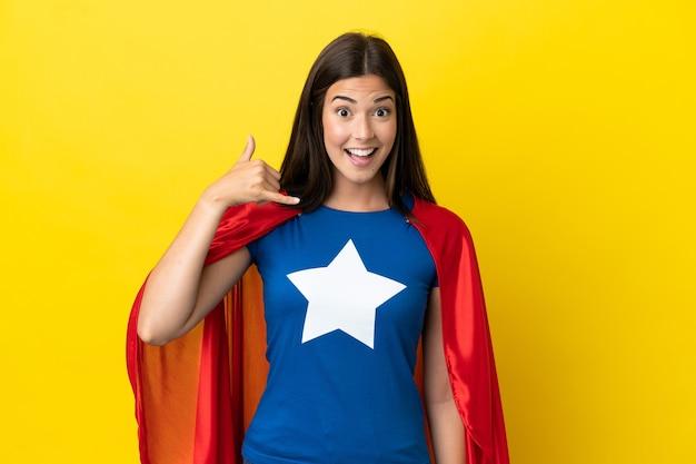 Super eroe donna brasiliana isolata su sfondo giallo che fa il gesto del telefono. richiamami segno