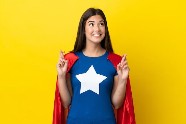 Super eroe donna brasiliana isolata su sfondo giallo con le dita incrociate