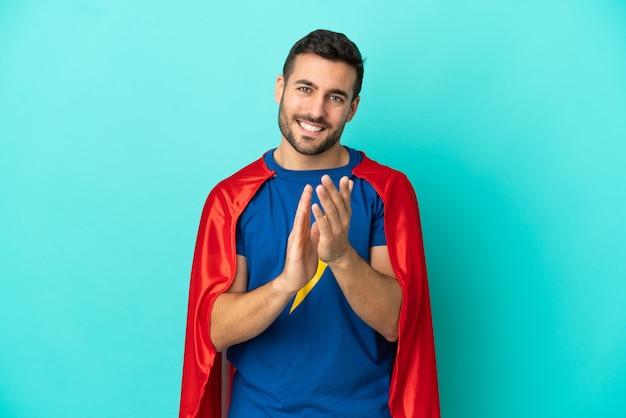 Uomo caucasico super eroe isolato su sfondo blu che applaude dopo la presentazione in una conferenza