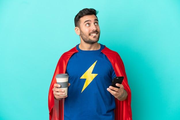 Uomo caucasico super eroe isolato su sfondo blu che tiene il caffè da portare via e un cellulare mentre pensa a qualcosa