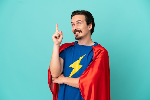 Uomo caucasico super eroe isolato su sfondo blu che indica una grande idea