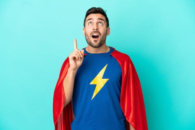 Uomo caucasico super eroe isolato su sfondo blu pensando a un'idea che punta il dito verso l'alto