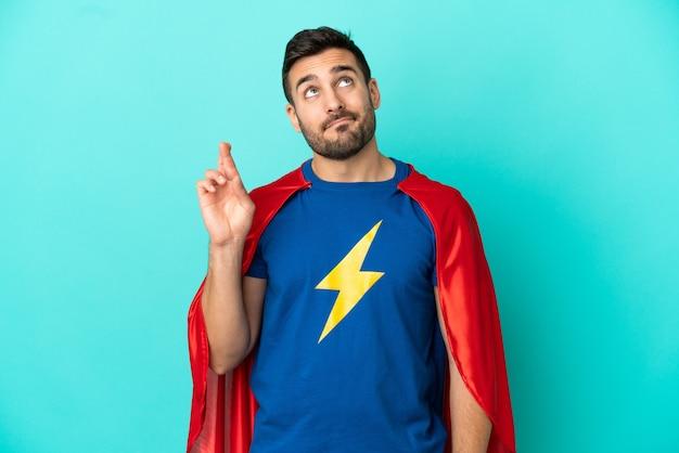 Uomo caucasico super eroe isolato su sfondo blu con le dita incrociate e augurando il meglio