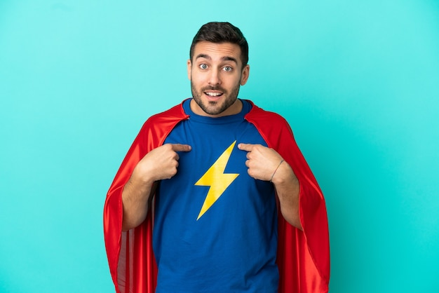 Uomo caucasico super eroe isolato su sfondo blu con espressione facciale a sorpresa