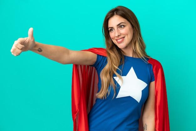 Donna caucasica del super eroe isolata su fondo blu che dà un gesto di pollice in alto