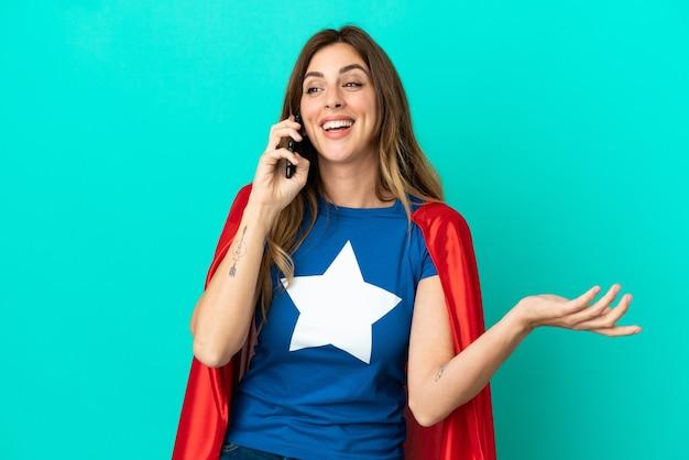 Donna caucasica super eroe isolata su sfondo blu che tiene una conversazione con il telefono cellulare con qualcuno